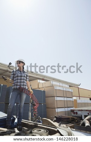 Mid adult woman holding a break hose while standing on logging truck - stock photo