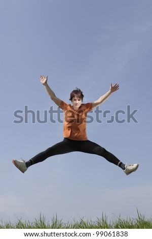 Mid adult woman jumping in the air - stock photo