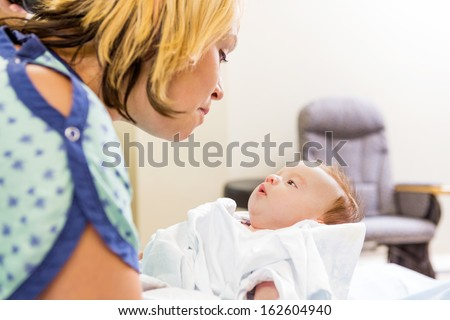 Mid adult woman looking at cute newborn babygirl in hospital room