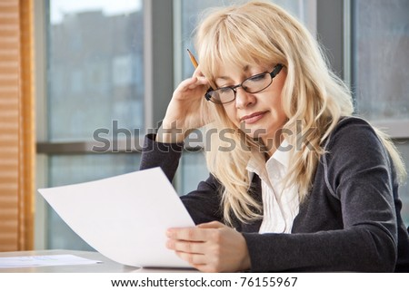 mid adult woman sitting at a table in the office against the window and work with documents - stock photo