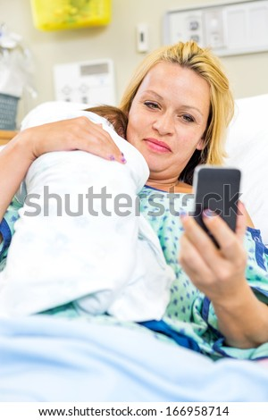 Mid adult woman taking self portrait with newborn babygirl through smart phone in hospital room