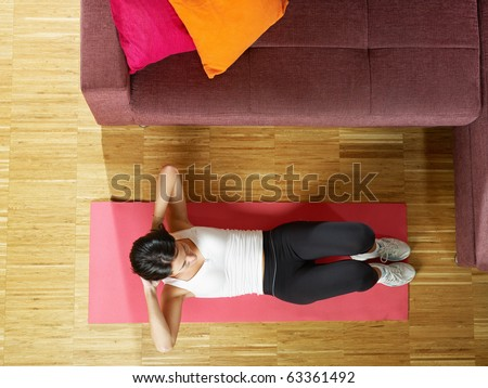 mid adult woman training abdominals at home. Horizontal shape, full length, high angle view, copy space - stock photo