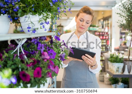 Mid adult woman using digital tablet while standing by trolley in flower shop - stock photo