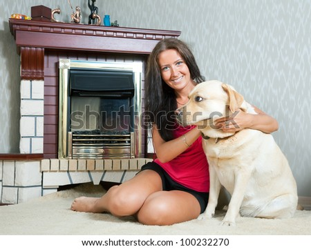 mid adult woman with  Labrador retriever  near the fireplace - stock photo