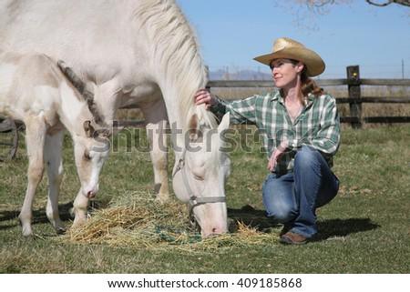 mid-adult woman with white horse and foal grazing on hay