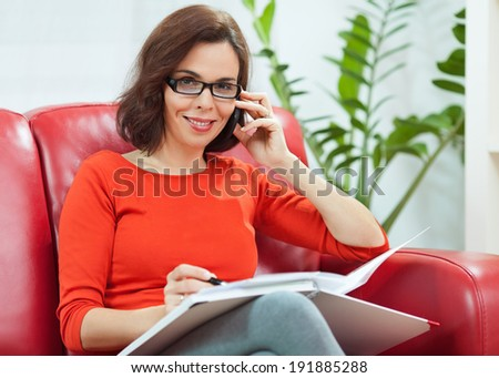 Mid adult woman working from home. - stock photo