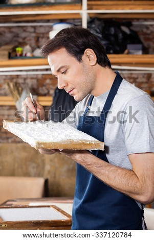 Mid adult worker removing dirt from paper in factory