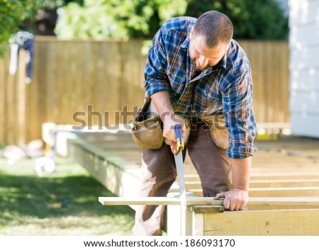 Mid adult worker sawing wood at construction site - stock photo
