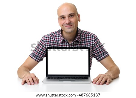 mid age bald man sitting at desk and using laptop. Blank screen with copy space. Isolated on white background