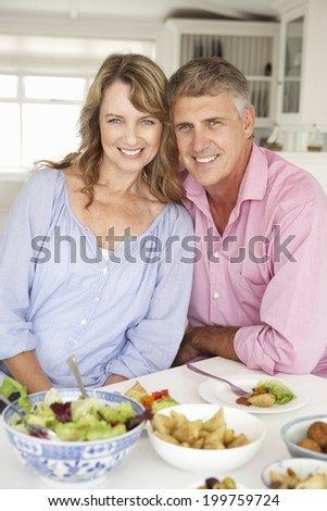Mid age couple enjoying meal at home - stock photo