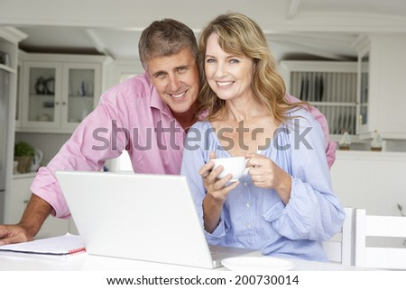 Mid age couple working at home on laptop - stock photo