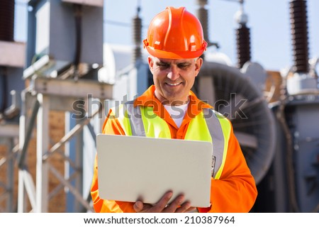 mid age engineer using laptop computer in electricity power plant