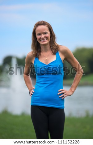 Mid Age Fitness Trainer Woman Outdoor Standing in front of Park Water Fountain - stock photo