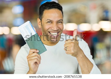 mid age man holding boarding pass and giving thumb up - stock photo