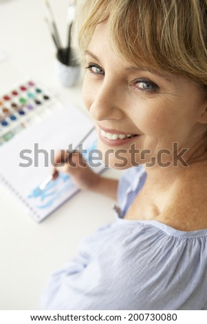 Mid age woman painting with watercolors - stock photo