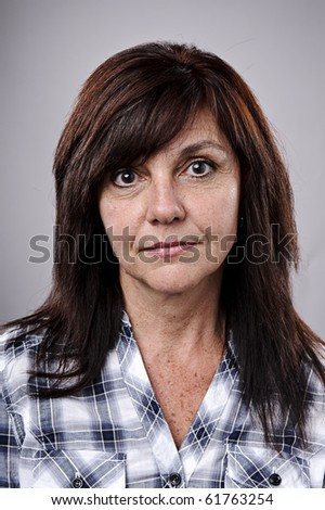 Mid age woman poses for a portrait in studio - stock photo