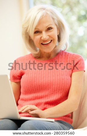 Mid age woman using laptop at home - stock photo