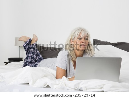 Mid age woman with a laptop lying down in bed - stock photo