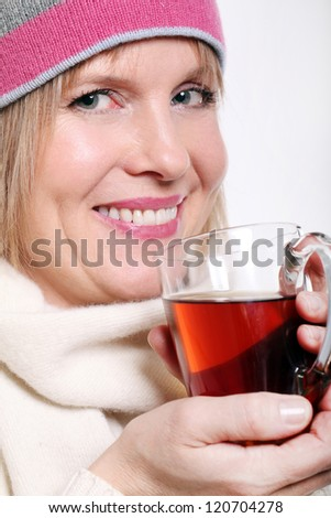 Mid age Woman With Hot tea Wearing Winter Clothes on a white background - stock photo