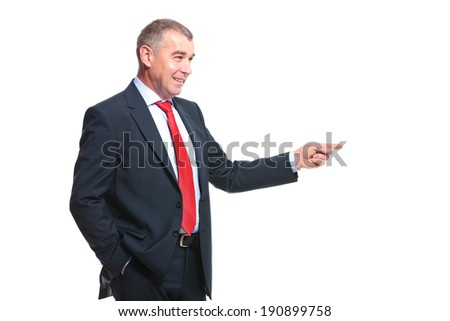mid aged business man pointing to his side while smiling and holding a hand in his pocket. isolated on a white background