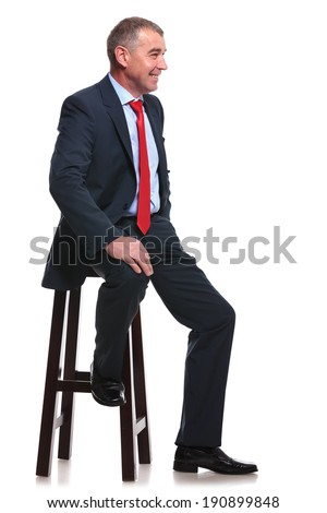 mid aged business man sitting on a chair and smiling away from the camera. isolated on a white background - stock photo