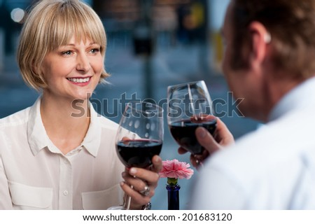 Mid aged couple toasting with glasses of wine - stock photo