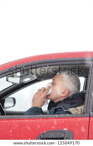 Mid aged man with flu symptoms sneezes in a car on snowy  winter day. Using handkerchief closes mouth with his hands