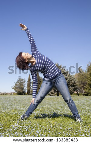 Mid aged woman doing streching yoga exercises outside in the garden - stock photo