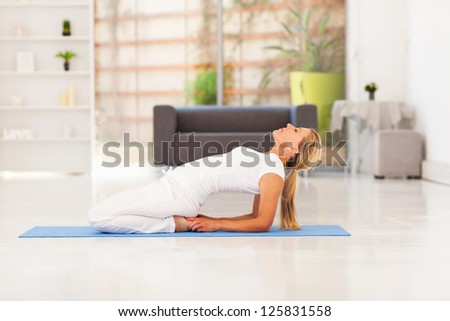 mid aged woman doing yoga at home - stock photo