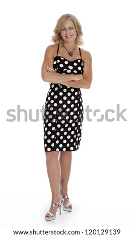 Mid-forties woman standing on white background wearing polka-dot dress with arms crossed