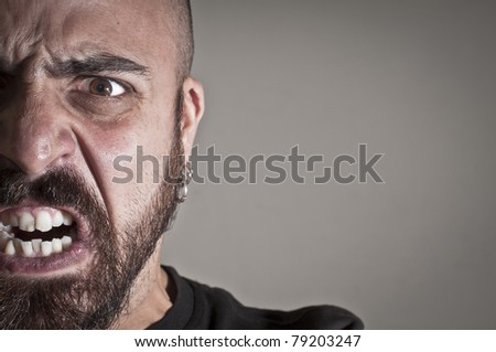 mid-frontal portrait of a man yelling on grey background