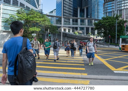 MID-LEVELS, HONG KONG - JUNE19: Unidentified people crossing road in front of The Peak Tram on June 19,2016 in Hong Kong.  - stock photo