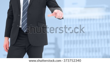 Mid section businessman pointing with his finger against low angle view of city buildings - stock photo