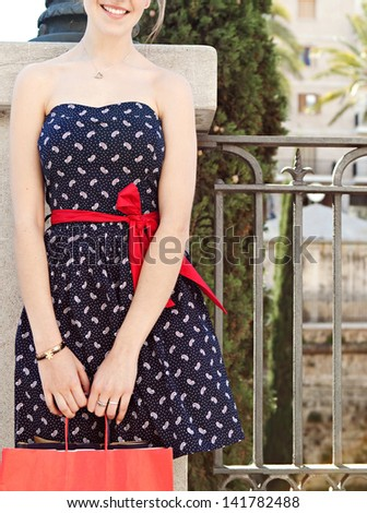 Mid section figure of a young woman in a city street holding paper shopping bags and wearing a sophisticated dress during a sunny day on vacation. - stock photo