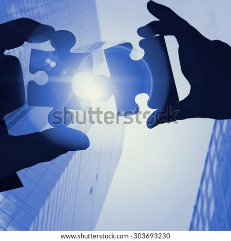 Mid section of a businessman in suit with hands out against skyscraper - stock photo