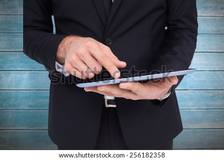 Mid section of a businessman touching digital tablet against wooden planks - stock photo