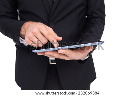 Mid section of a businessman touching digital tablet on white background