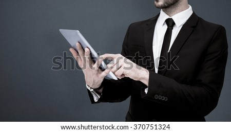 Mid section of a businessman using digital tablet pc against grey background - stock photo
