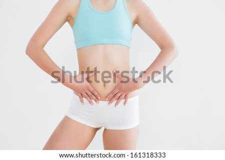 Mid section of a fit woman in sportswear with hands on belly against wall in fitness studio