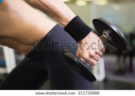 Mid section of a fit young woman exercising with dumbbell in the gym