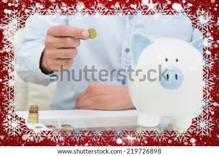 Mid section of a man putting some coins into a piggy bank against snow