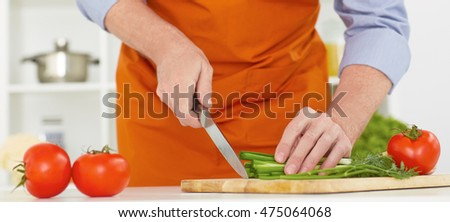 Mid section of a man with a knife cutting green onion on the kitchen background.