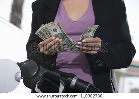 Mid section of a woman counting money while refueling car - stock photo