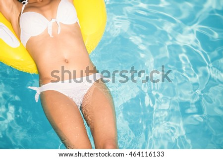 Mid section of a woman in white bikini floating on inflatable tube in swimming pool on a sunny day