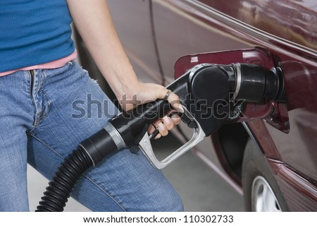 Mid section of a woman refueling her car at a fuel station