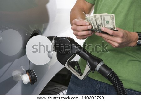 Mid section of a young man counting money while refueling car - stock photo
