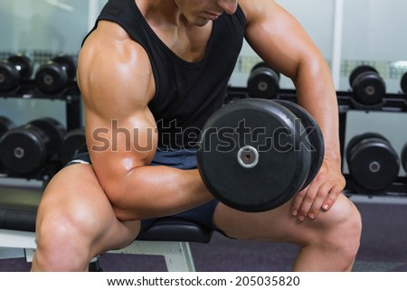 Mid section of a young muscular man exercising with dumbbell in gym - stock photo