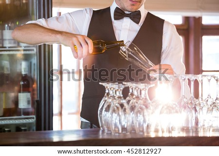 Mid section of bartender pouring a beer in a glass at bar counter