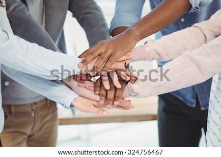 Mid section of business team putting their hands together at office
