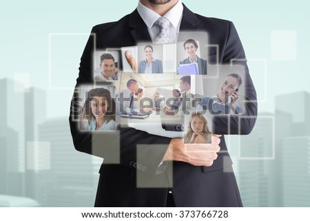 Mid section of businessman holding computer against blue background